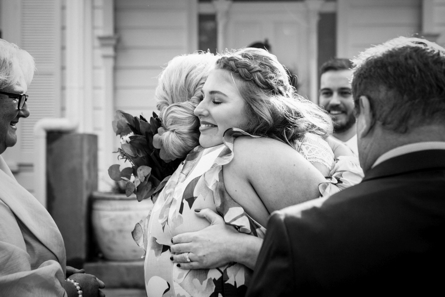 Documentary style image of bride as she hugs her family with a smile after marrying in Tasmania.