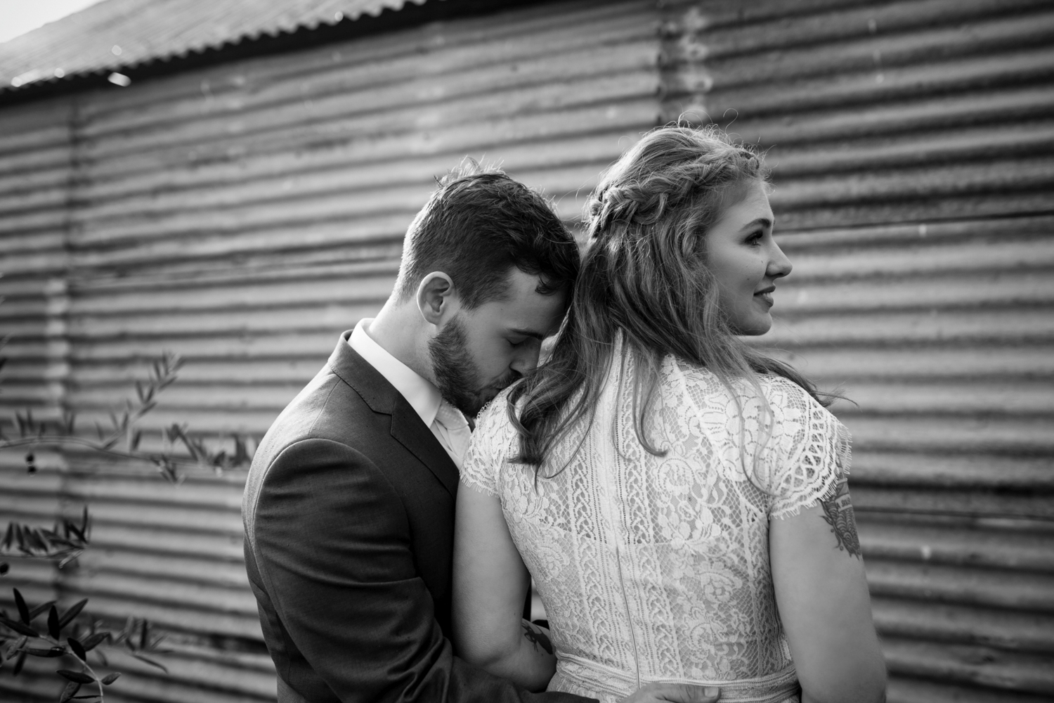 Groom kisses shoulder of bride in front of character shed at quamby house tasmania.