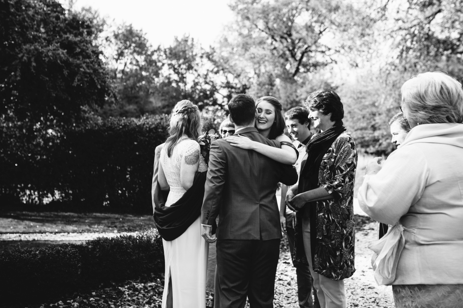 Family embraces bride and groom after wedding ceremony in northern tasmania.