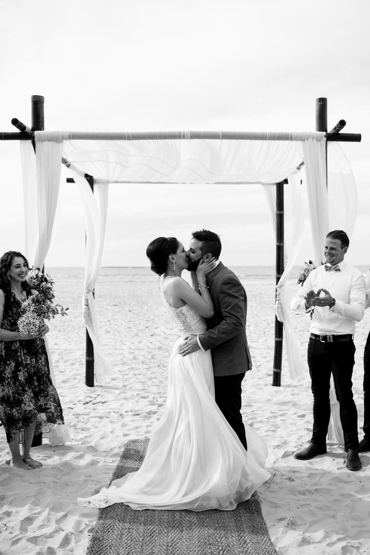 Couple kiss at a beach wedding in Queensland.