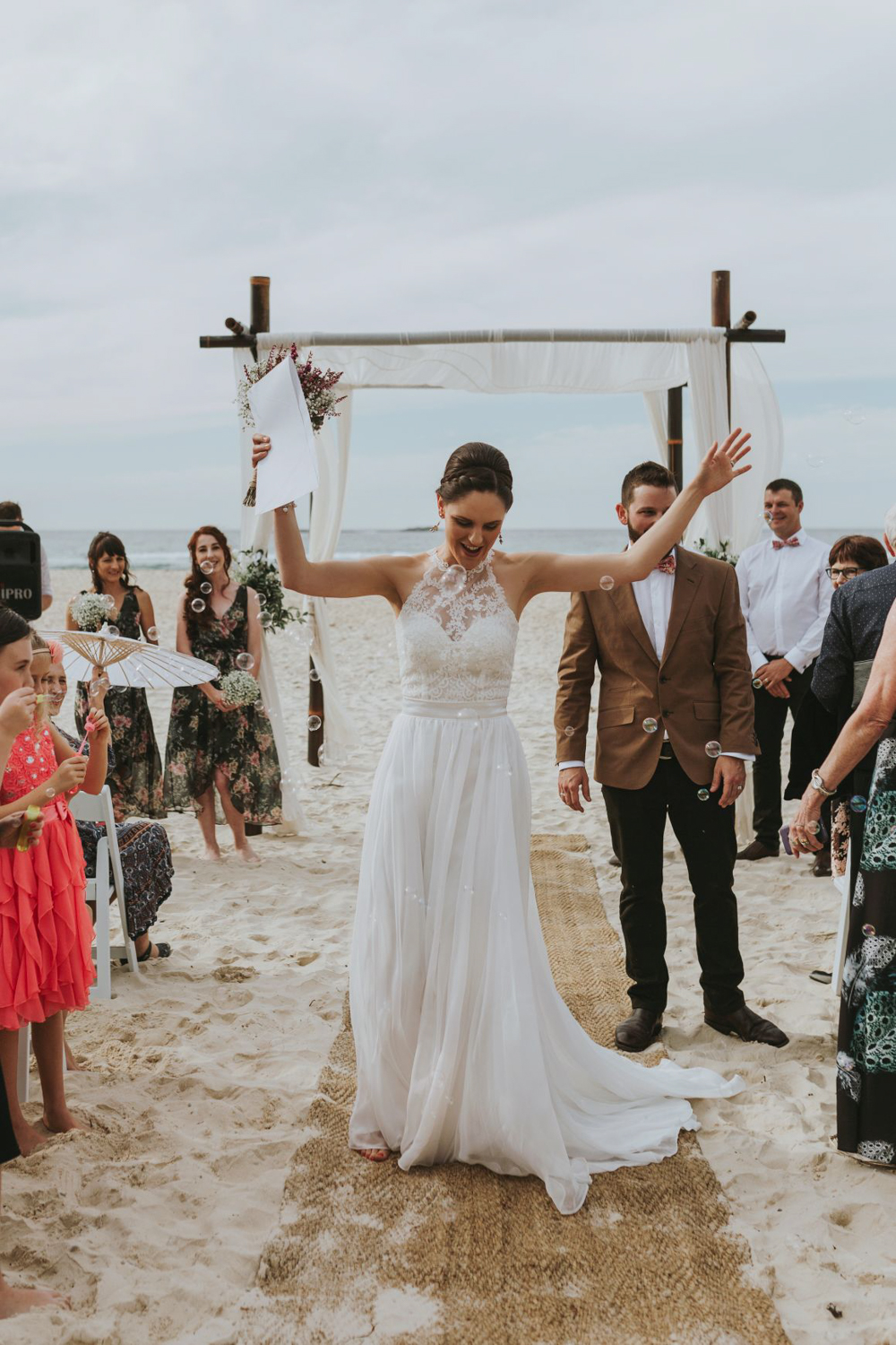 Bride celebrates marrying her husband at a beach wedding in Queensland