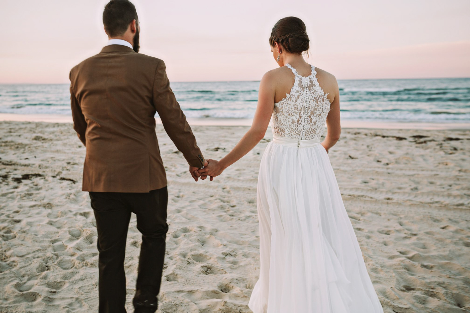 Couple walks towards the turquoise ocean after getting married at point lookoutcouple walks towards the turquoise ocean after getting married at point lookout.