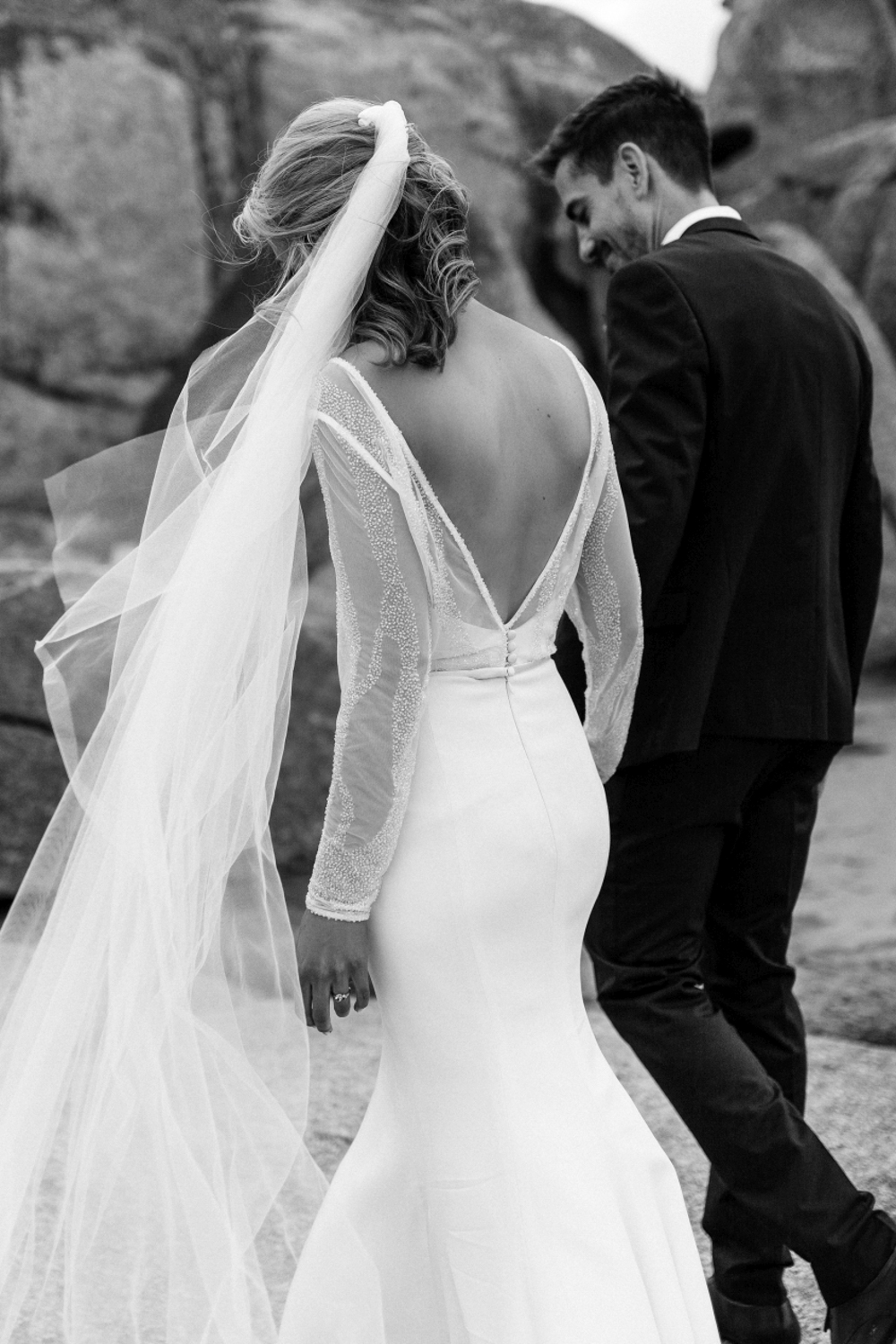 bride and groom walk on rocks in a beautiful classic image of the back of brides beautiful gown in Tasmania.