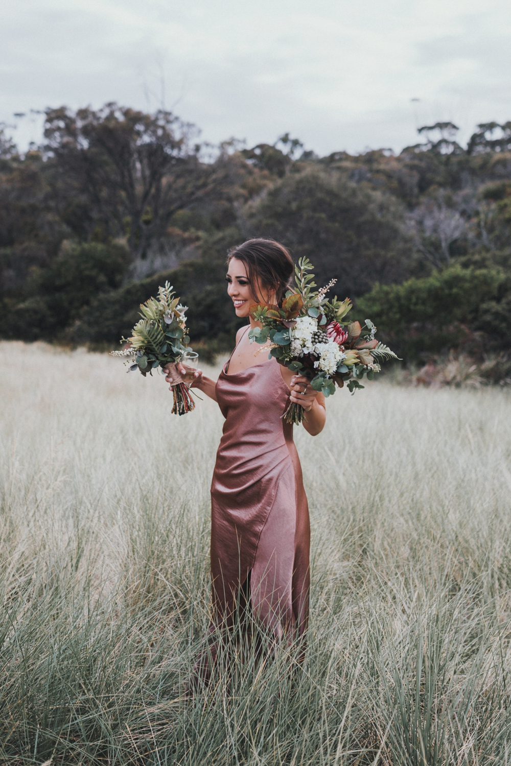 bridesmaid hold bouquets in the dunes of a bay of fires beach after wedding.