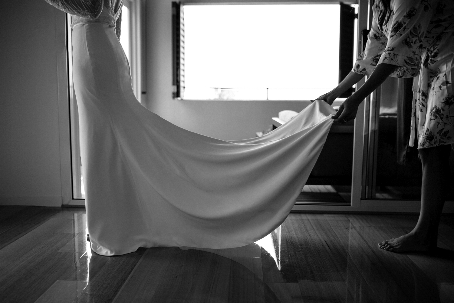 bridesmaid adjusts train of bridal gown in preparation for a wedding at bay of fires tasmania