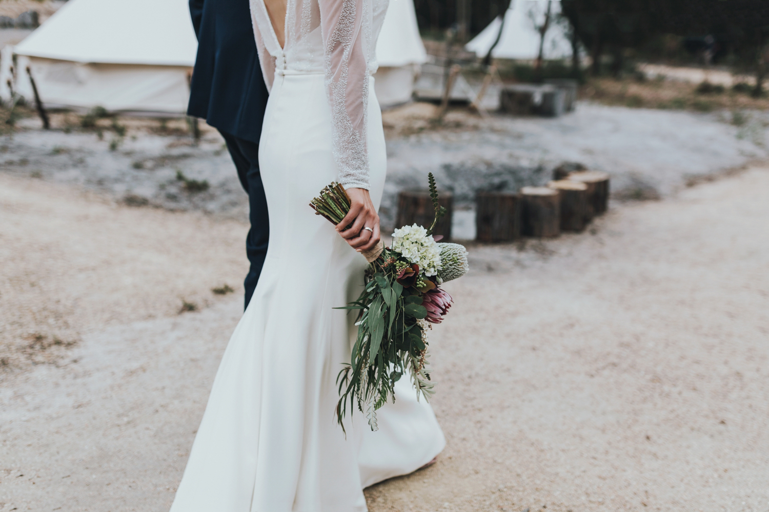 bride walks with native bouquet down a sandy path at bay of fires bush retreat.