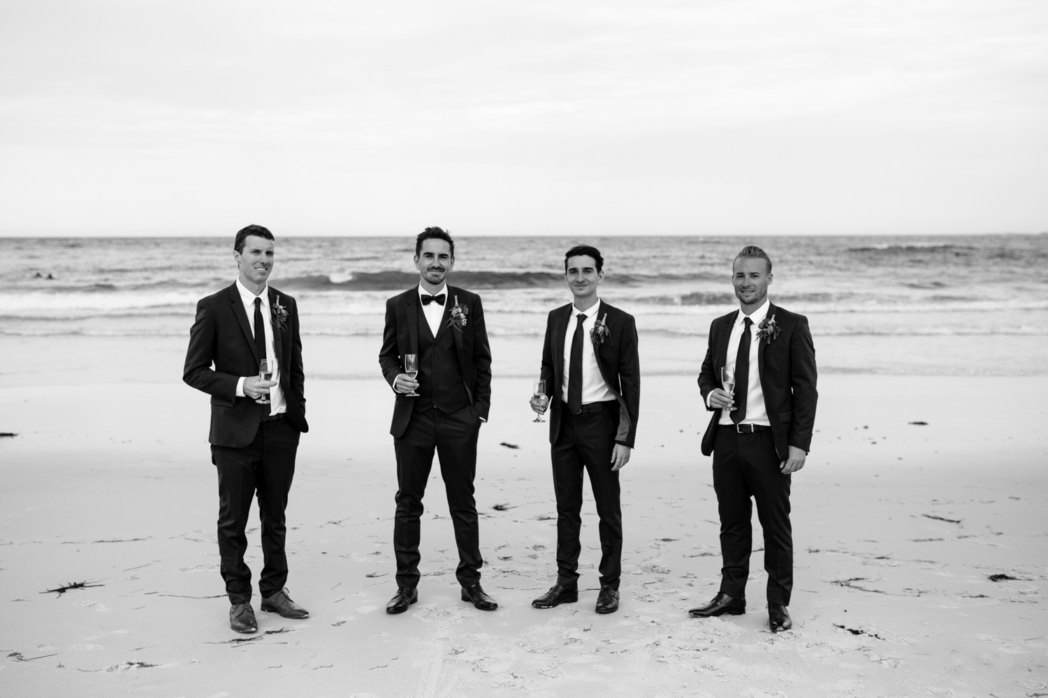 groomsmen stand with champagne at the beach after stylish wedding in Tasmania.