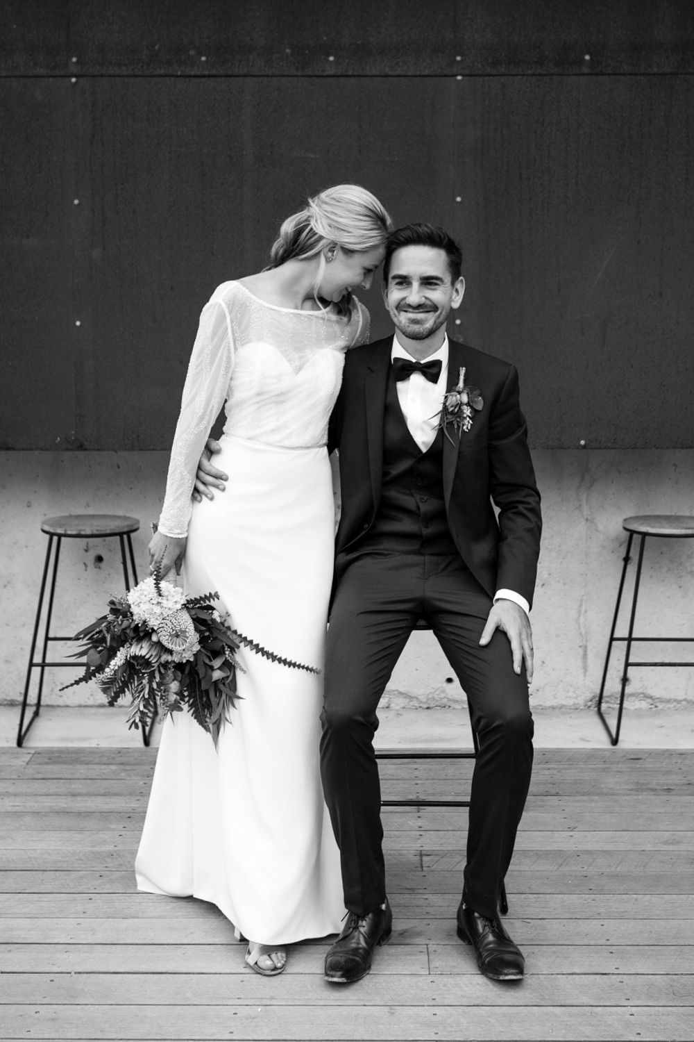 bride and groom smile with groom sitting and bride standing in stylish wedding at bay of fires bush retreat.