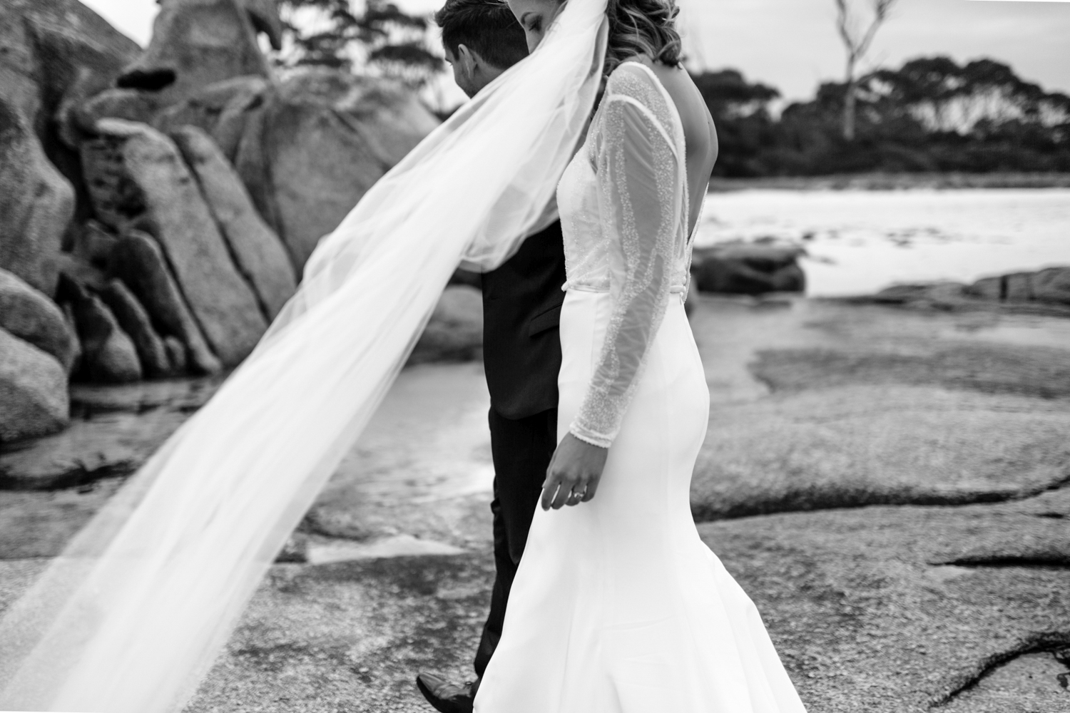 bride and groom walk on rocks at beach with veil blowing in the wind.