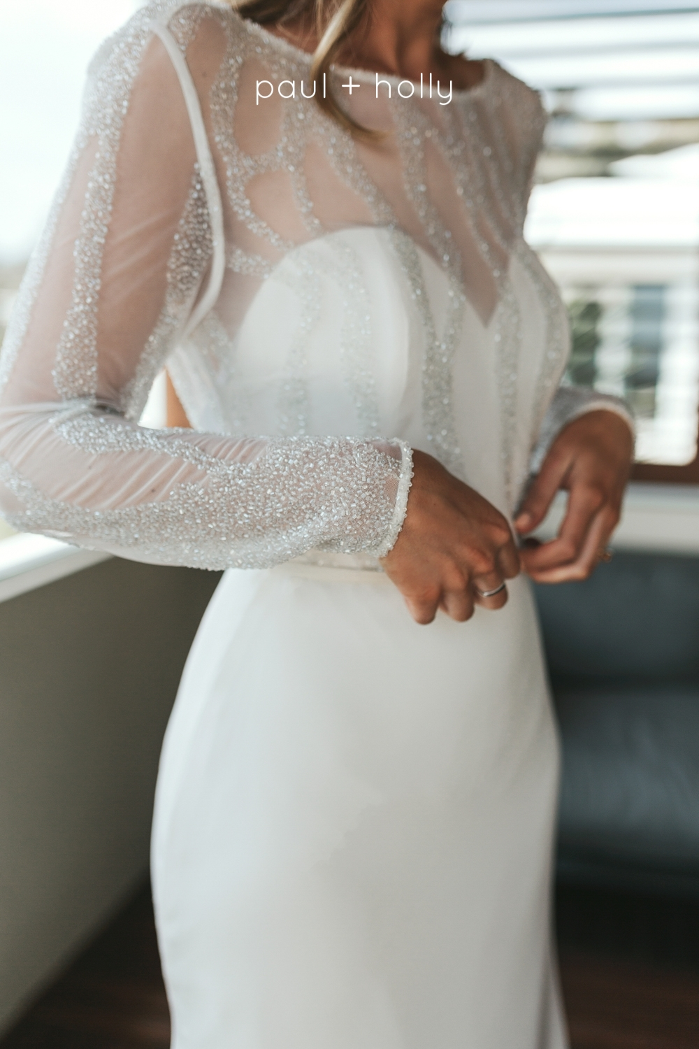 bride adjusts her dress in a beautiful custom designed gown for her wedding day at bay of fires tasmania