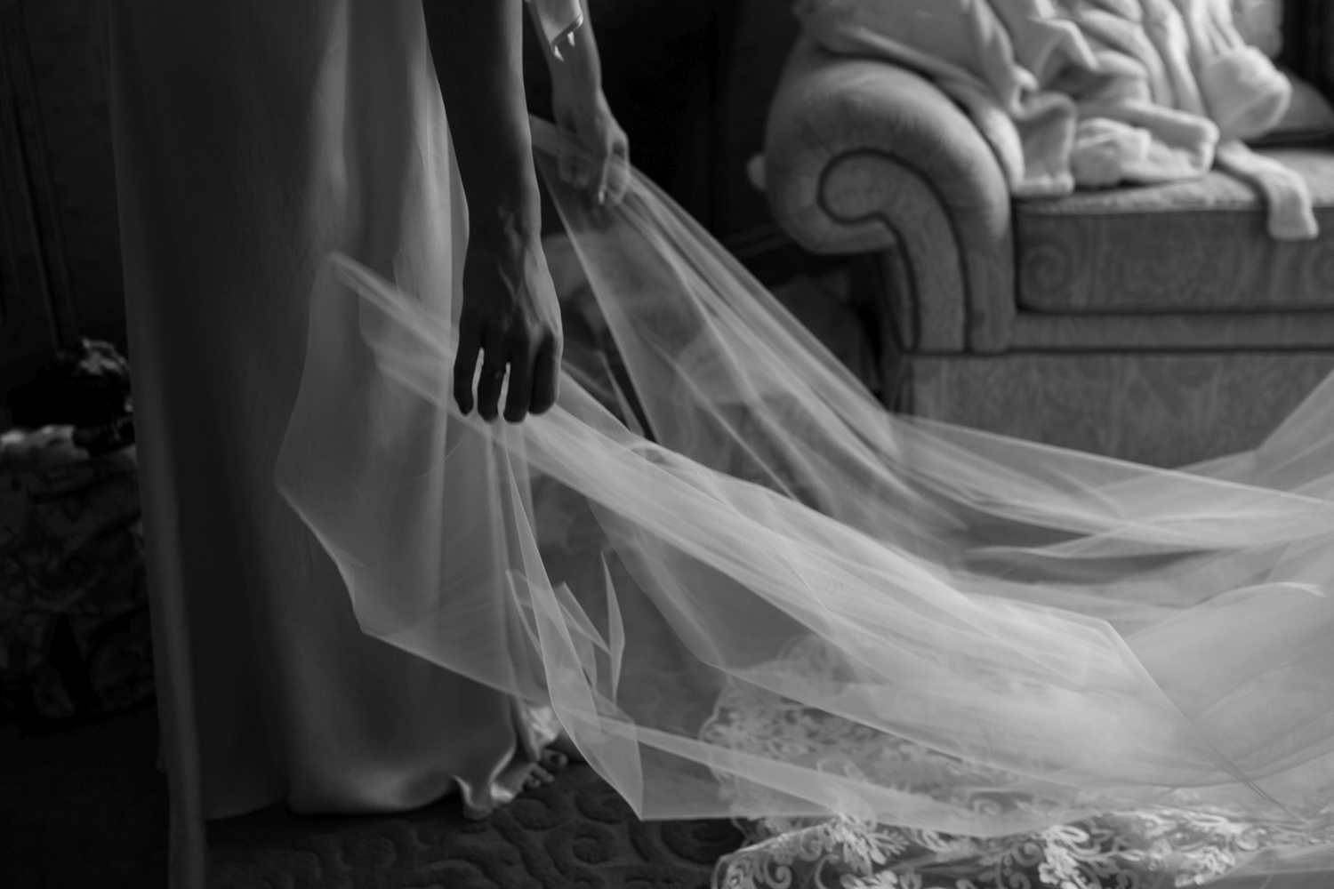 Bridemsaid adjusts veil of bride in a beautiful classic image by siida photography.