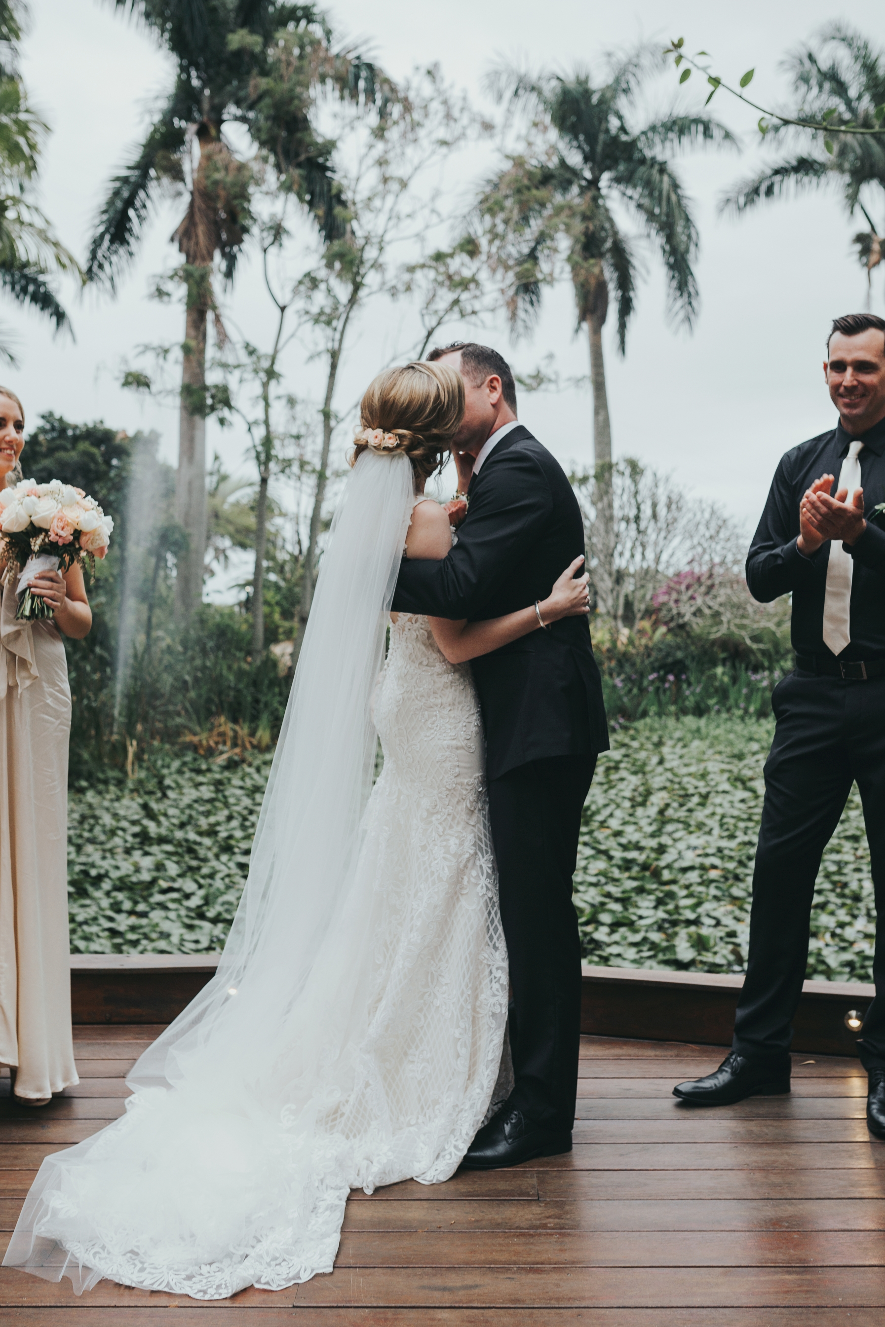 Bride and groom kiss at their wedding ceremony in front of a lake at a beautiful venue in Brisbane.