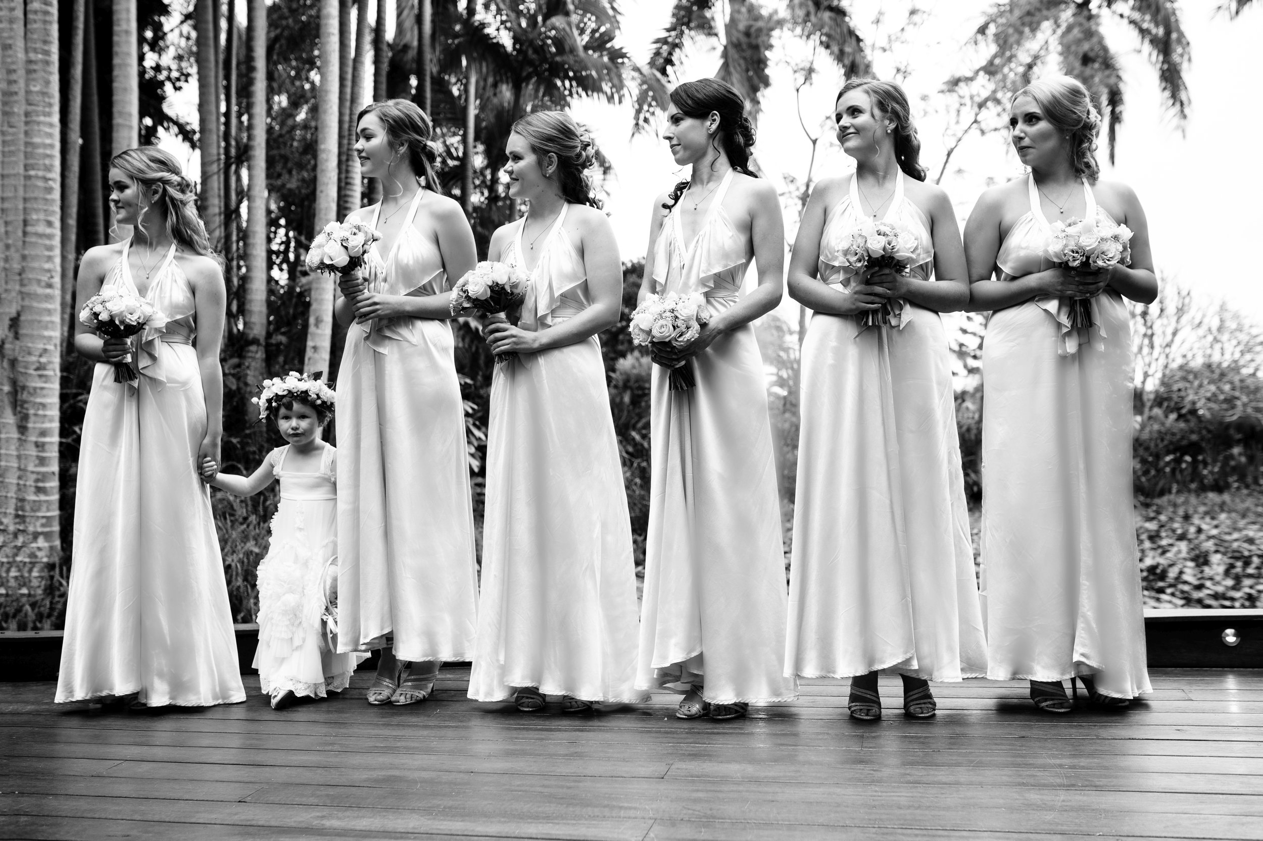Bridesmaids and flower girl stand during ceremony of wedding in Brisbane.