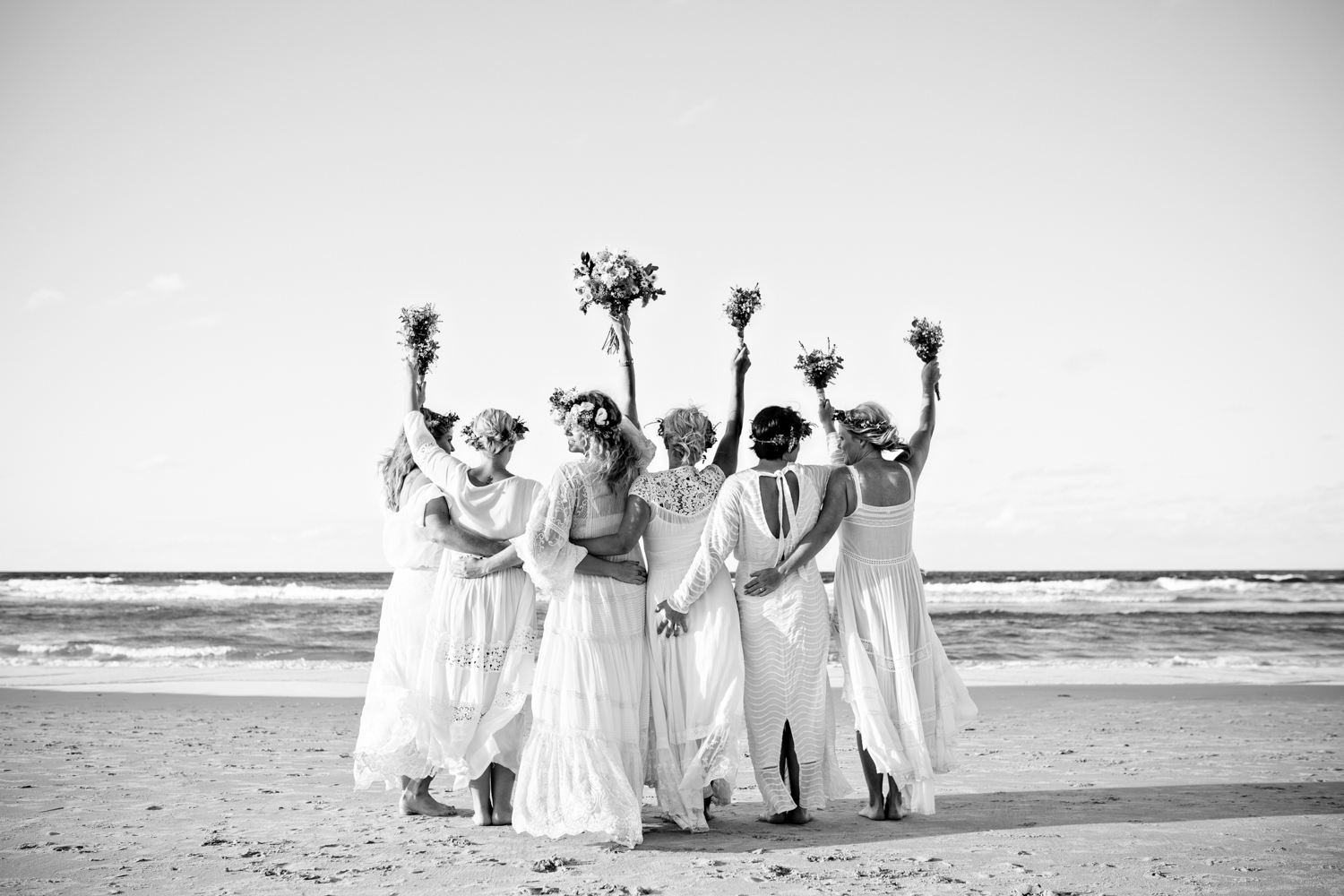 bridesmaids hold their bouquets in the air celebrating the wedding of the bride.