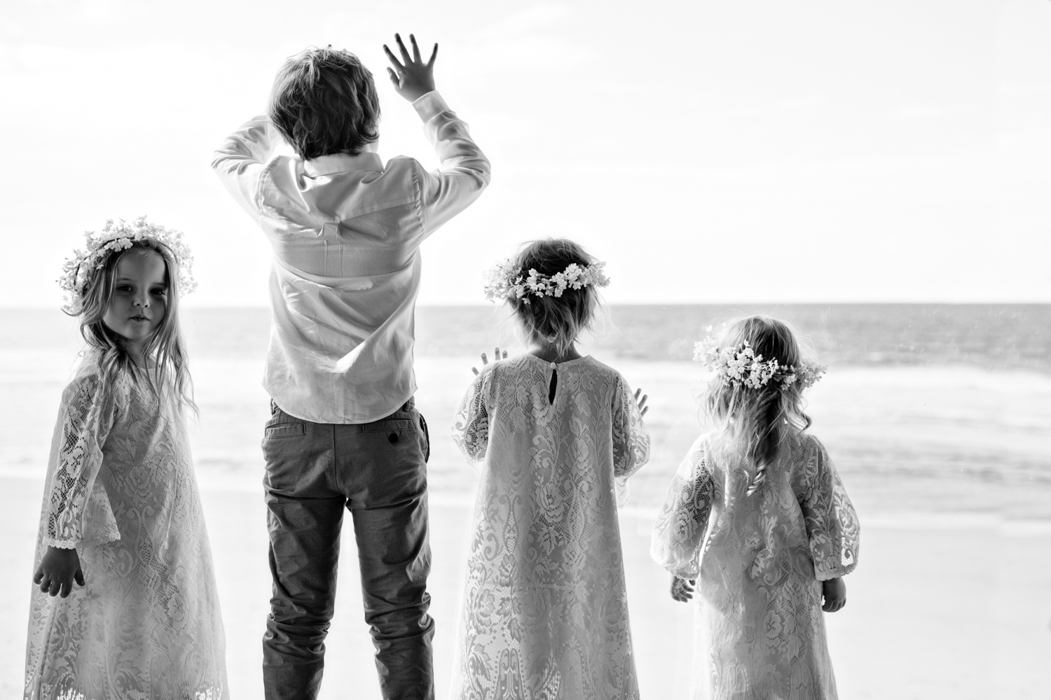 beautiful image of flower girls and page boy looking out to the ocean in Byron Bay.
