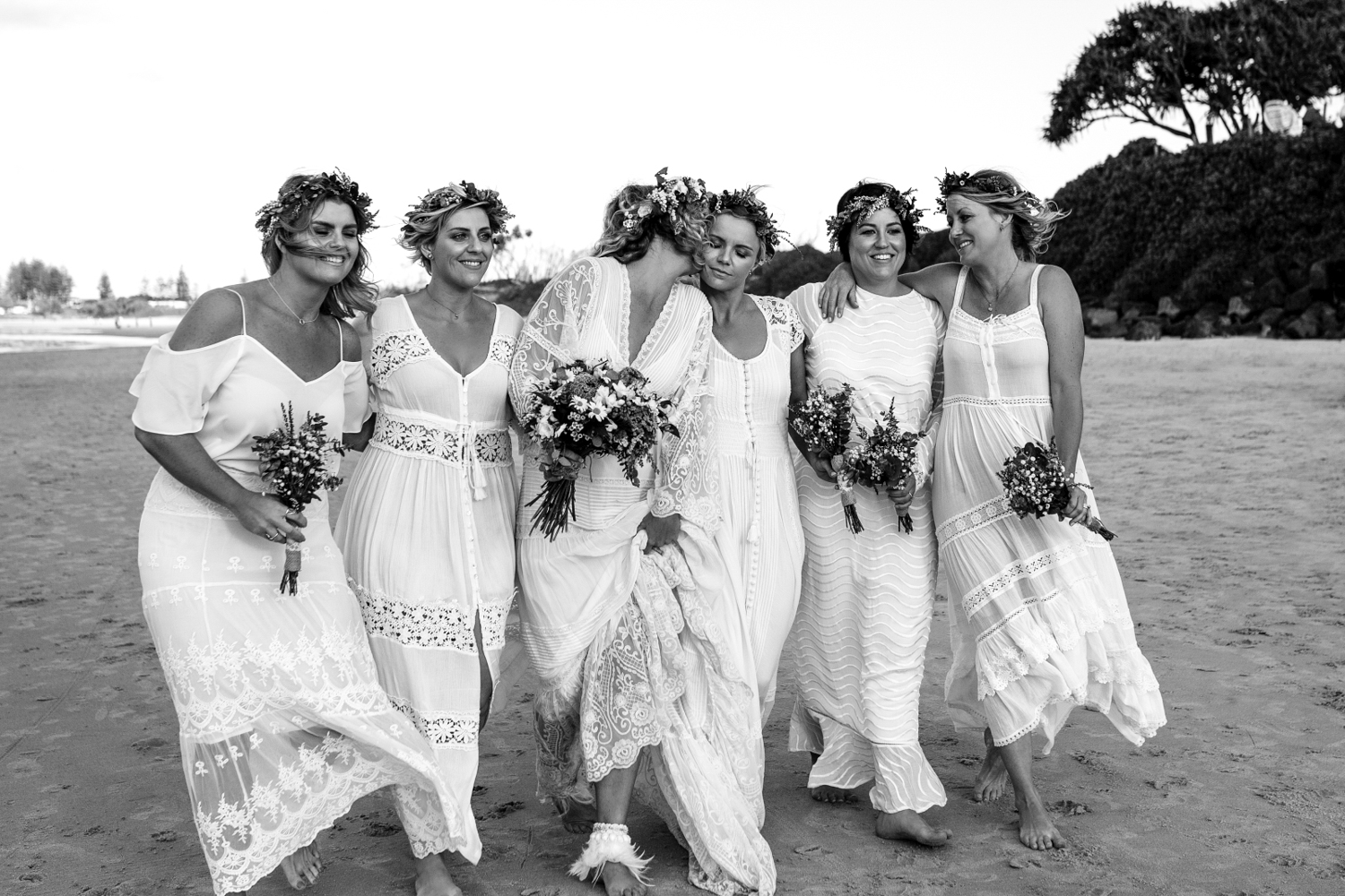 bride kisses her maid of honour as they stroll with bridesmaids on the beach.