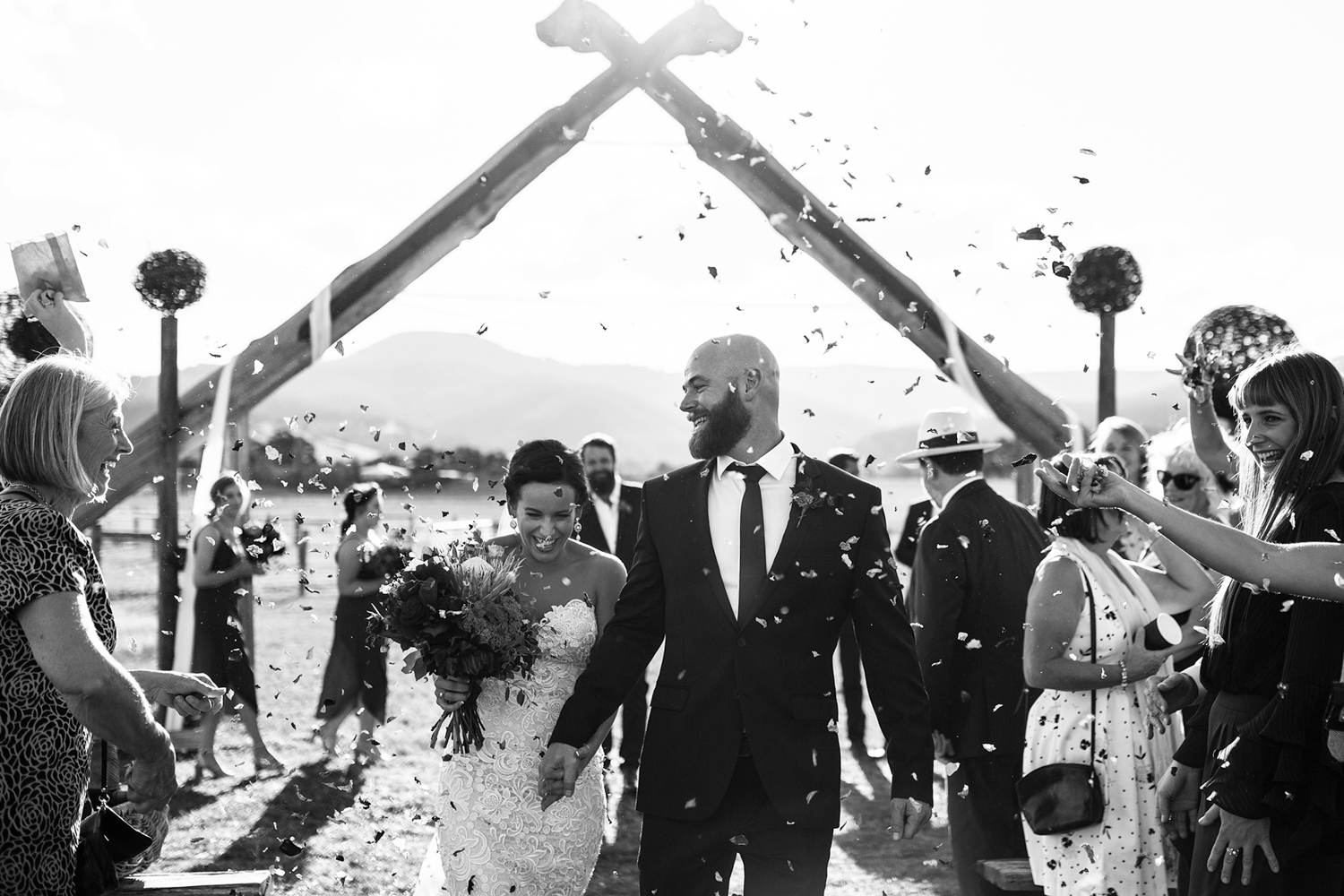 Couple smile as confetti is thrown after their wedding at Willie Smiths Apple Shed.