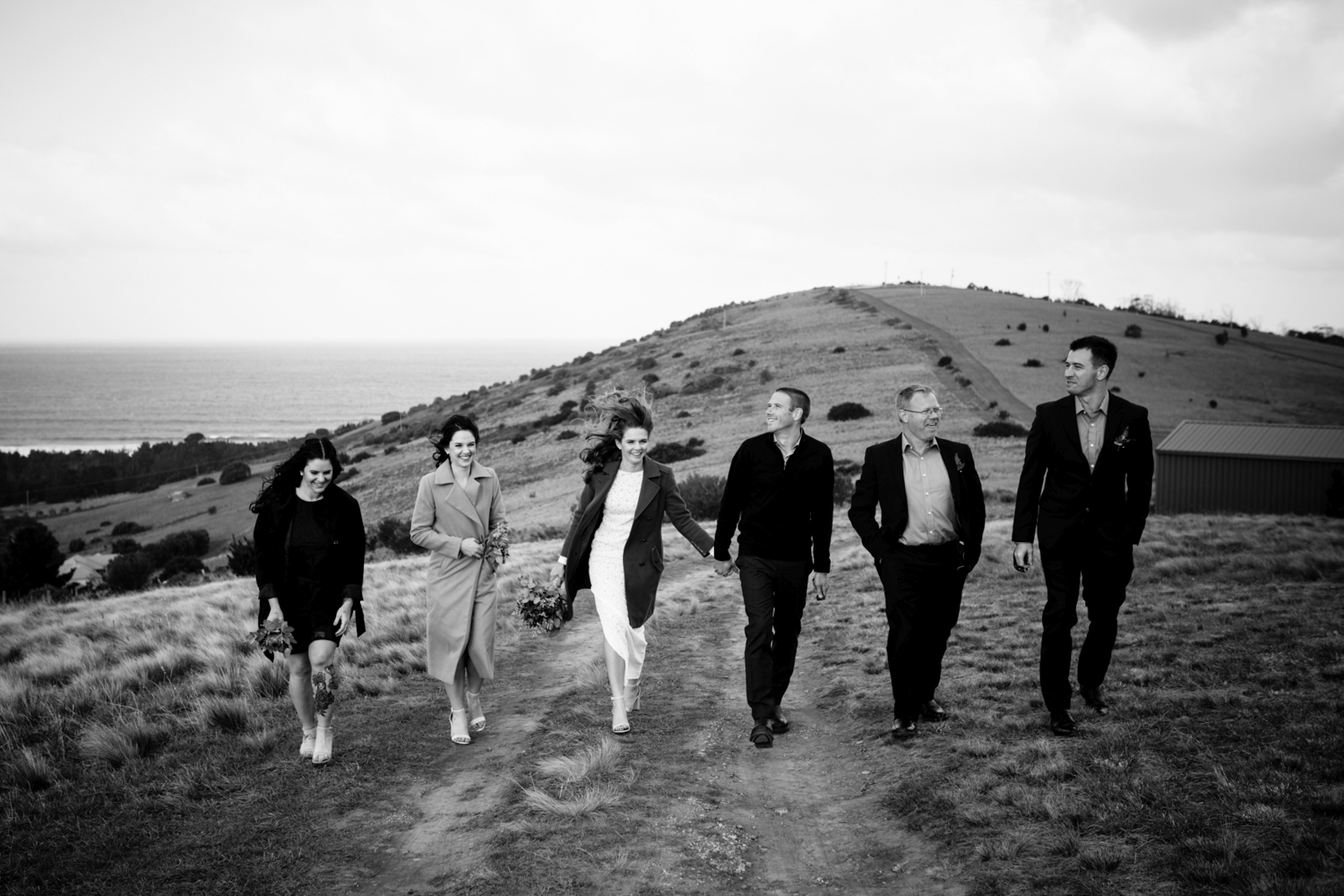 Bridal party walk on the coast on a windy day with brides hair blowing in Tasmania.