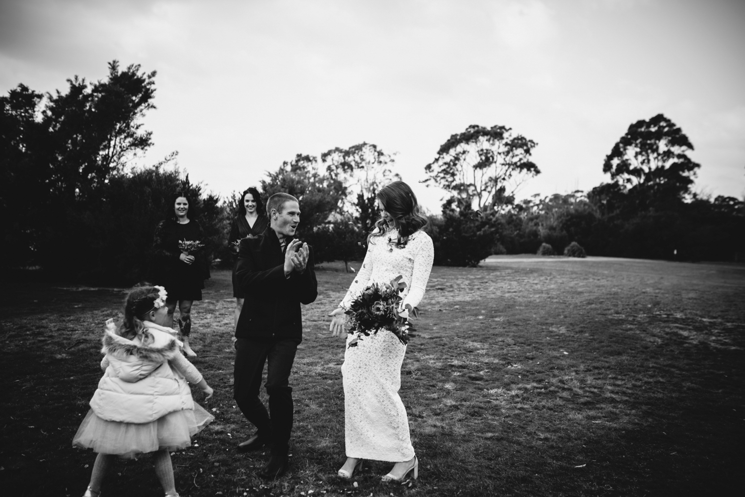 bride squeals after confetti thrown at her by young girl after wedding ceremony in tasmania.