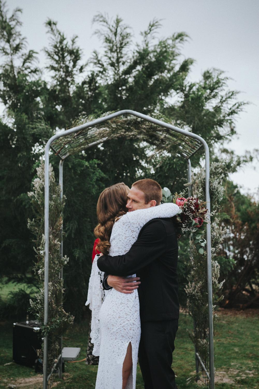 bride and groom hug after getting married in south arm tasmania.