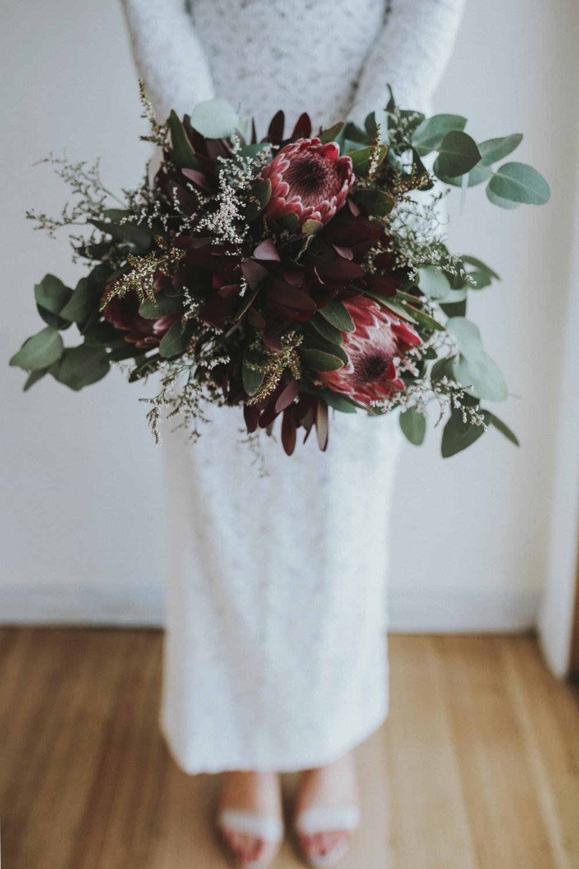 Bride holds native bouquet.