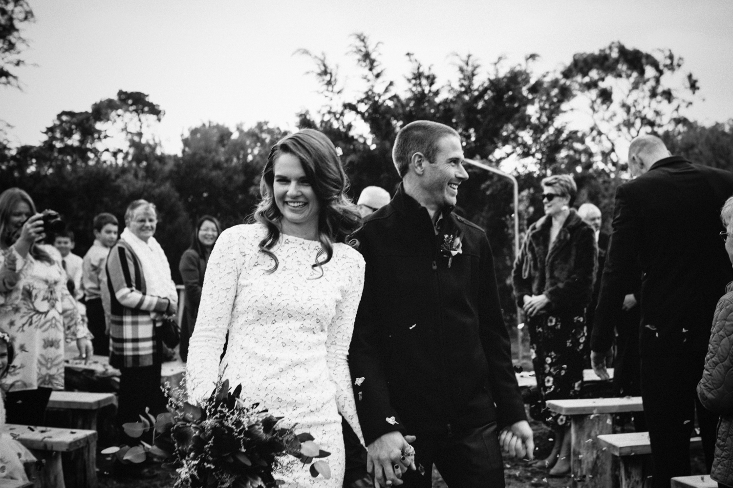 married couple smile through confetti after their wedding ceremony in tasmania.