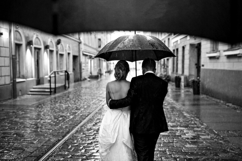 Bride and groom walk down shiny cobble stoned street in the rain under umbrella in Helsinki.