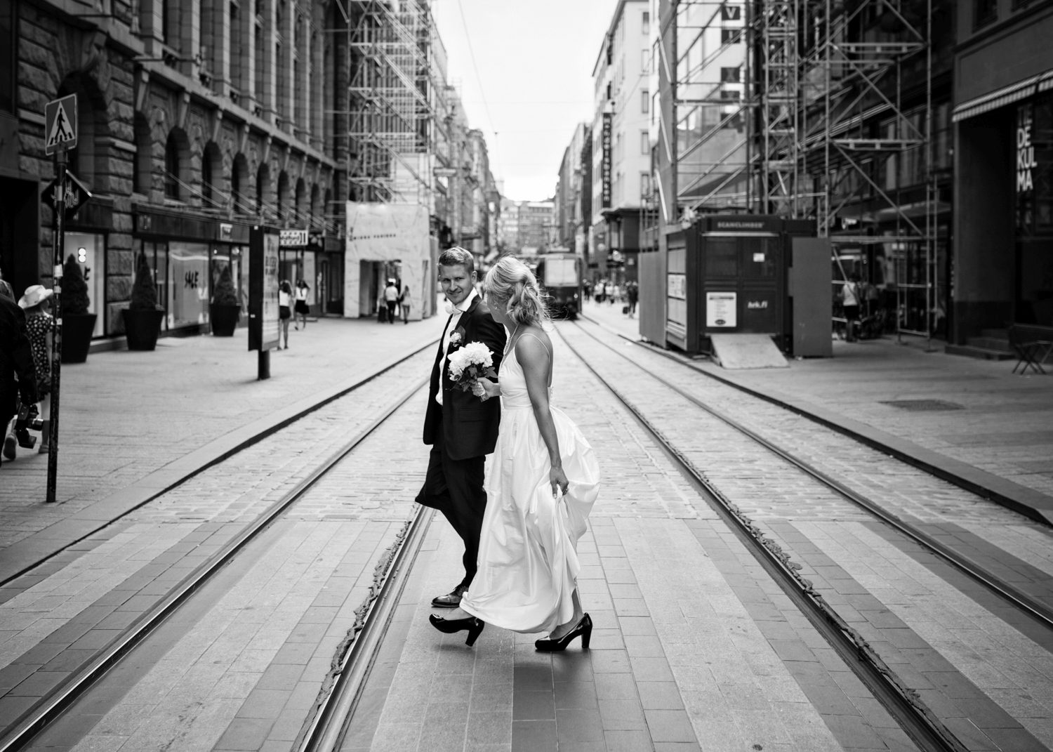 Bride and groom cross the street with tram lines in Helsinki Finland.
