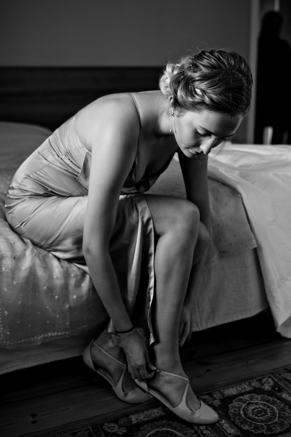 Bridesmaid puts on her shoes in hotel room before wedding in Helsinki Finland.