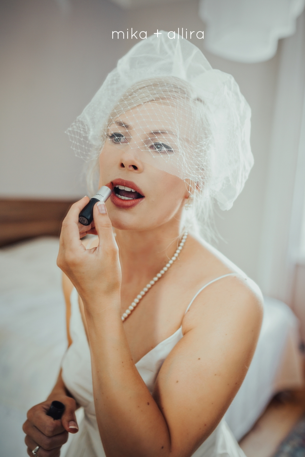 Bride puts on lipstick in hotel room before her wedding day in Helsinki Finland.