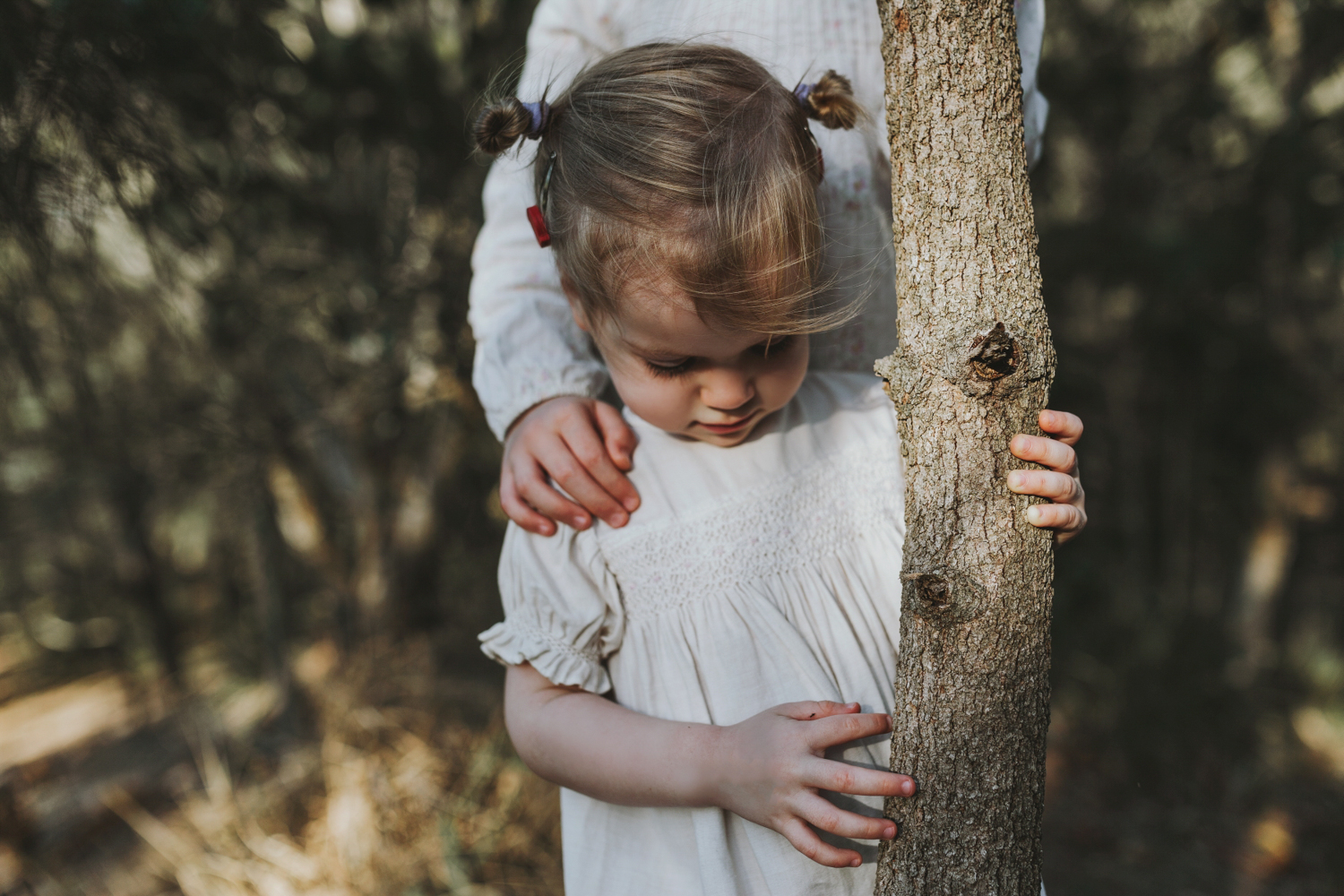 Girl plays with bark on tree as her sister rests her hand on her shoulder during a family session.
