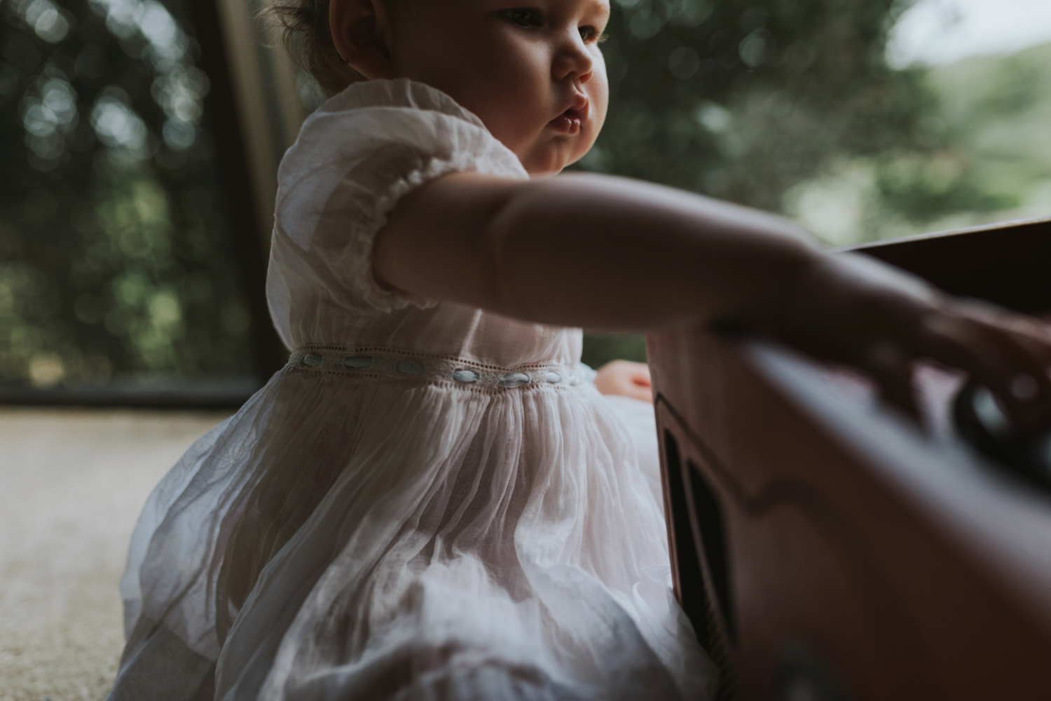 Baby plays with old record player in vintage lace dress during photo session in Brisbane.