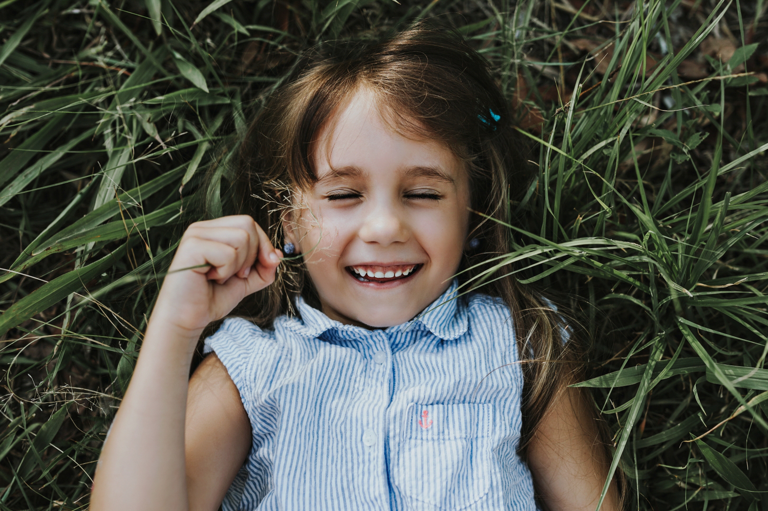 Family photography session with girl smiling in field tickling face with grass in Brisbane.