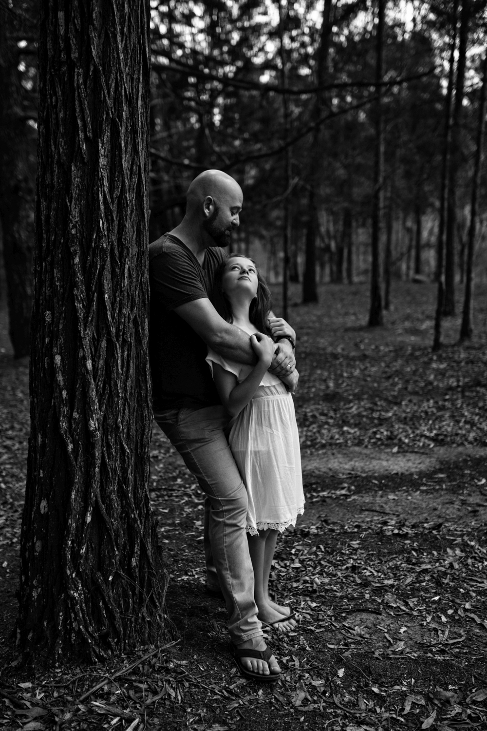 Daughter and father embrace during documentary family photo session.