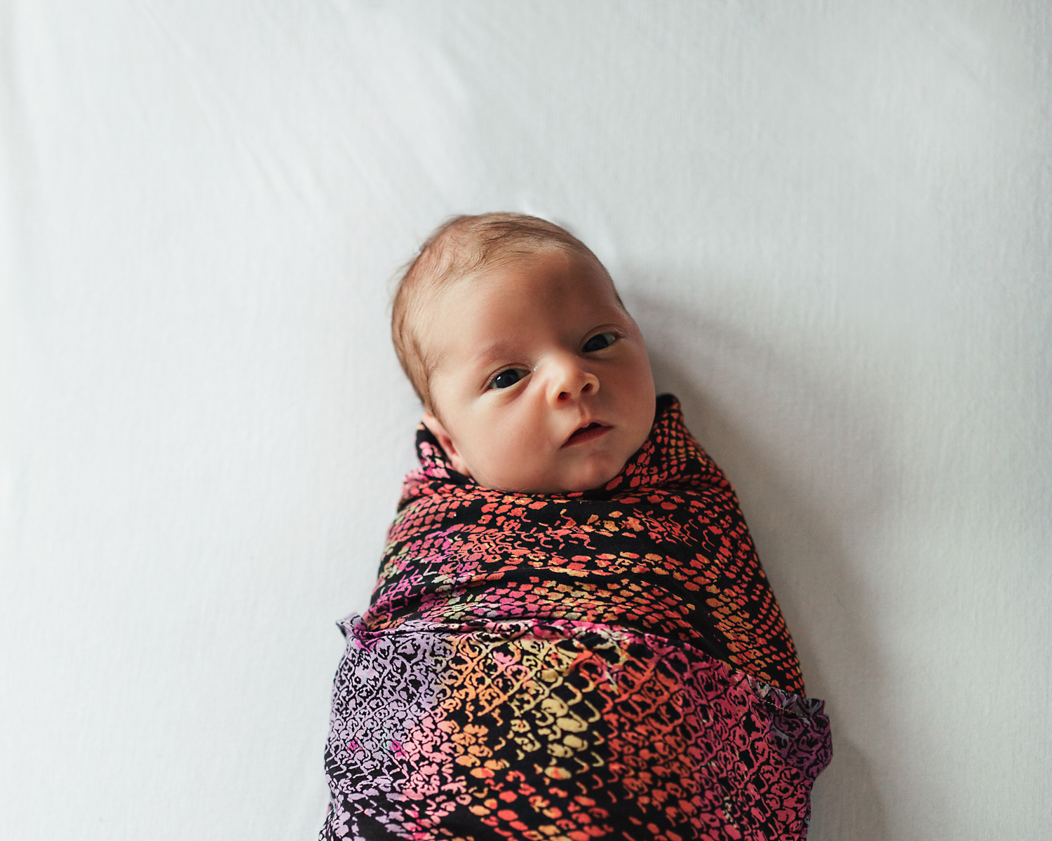 Newborn baby wrapped in children of the tribe baby wrap.