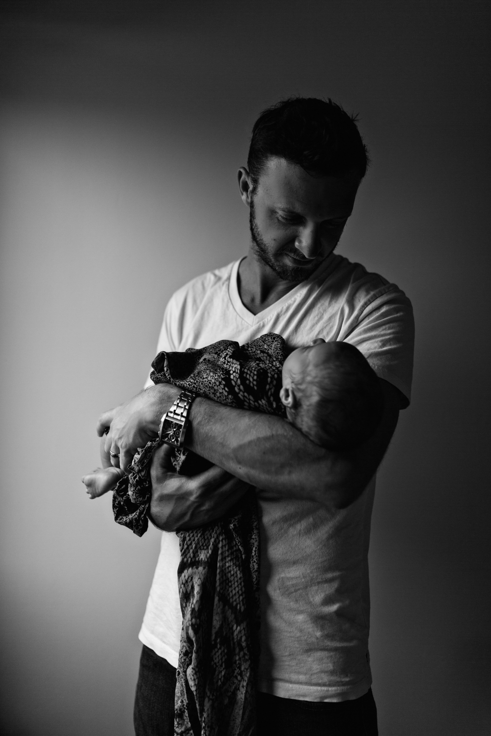 Father holds son and gazes at him during a newborn family photo session.