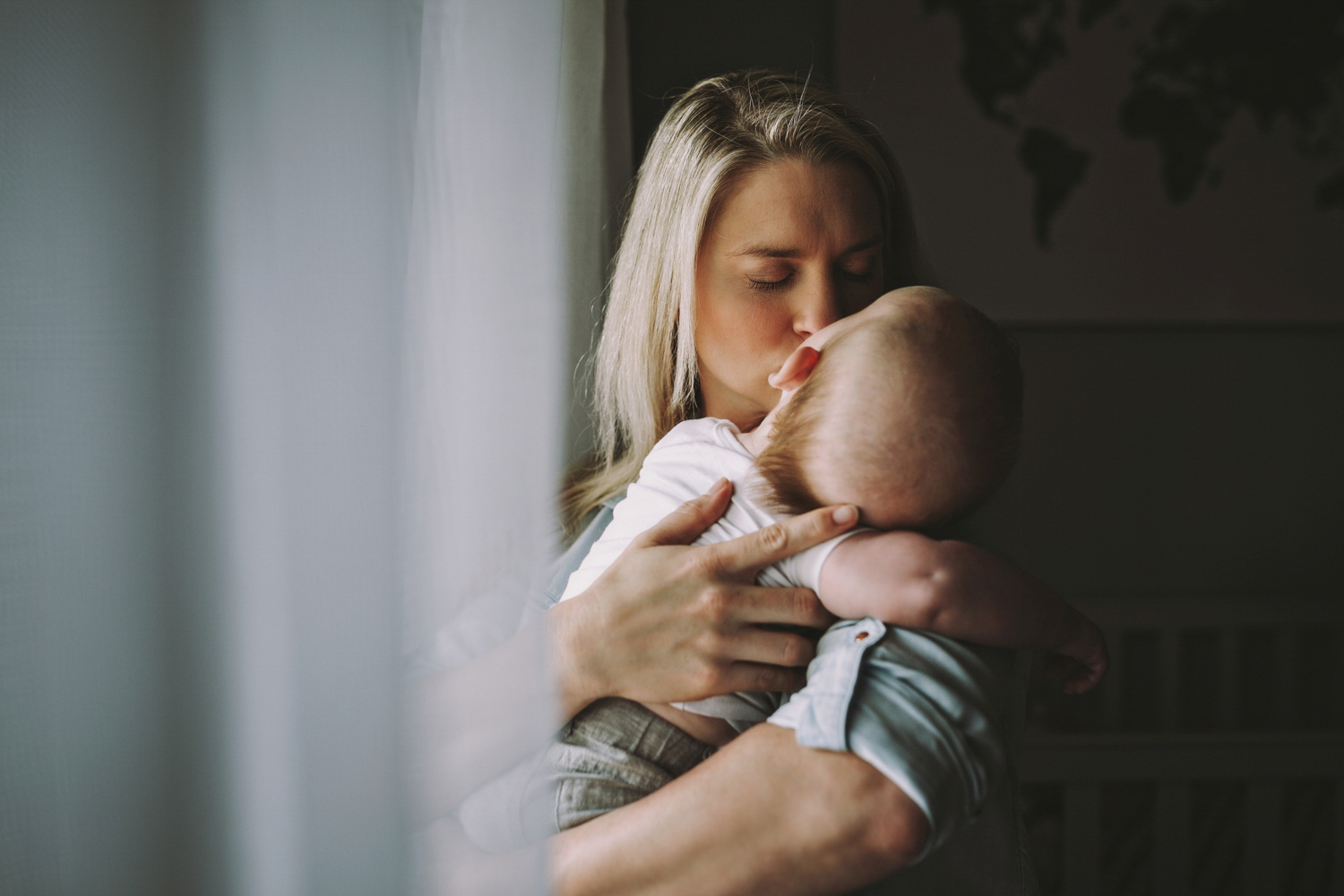 Mother kisses young baby in a lifestyle family portrait session in Brisbane.