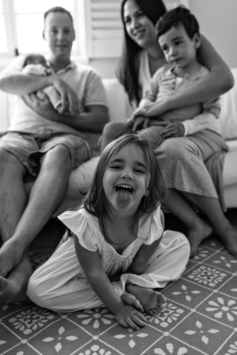 Cheeky girl pokes tongue at camera during lifestyle session in Tasmania.