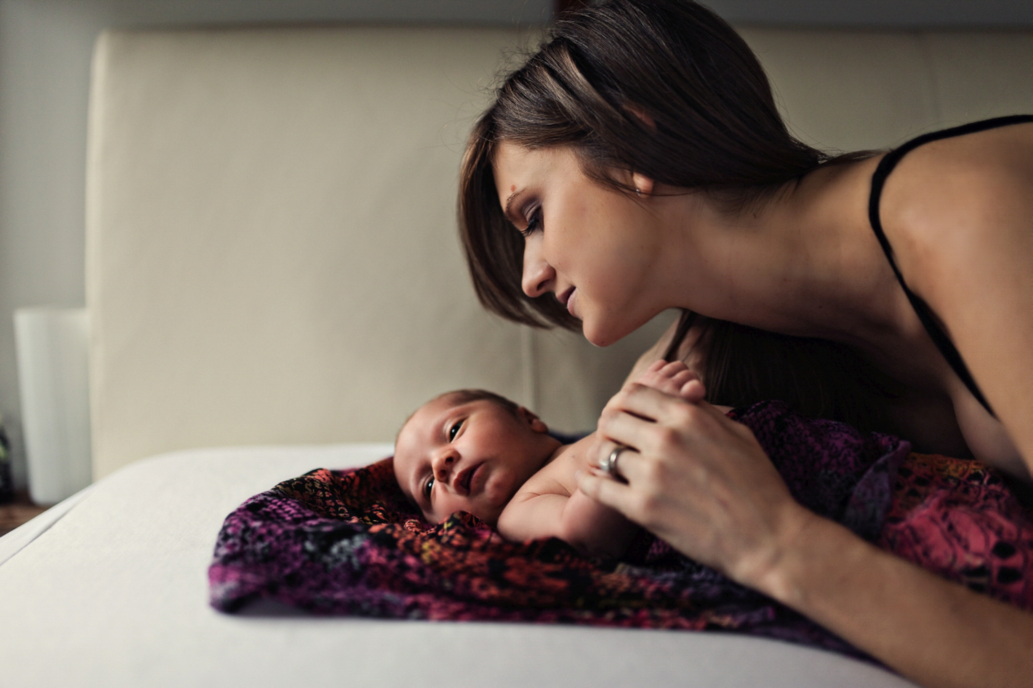 Mother gazes at her newborn baby in a documentary home session with siida photography.