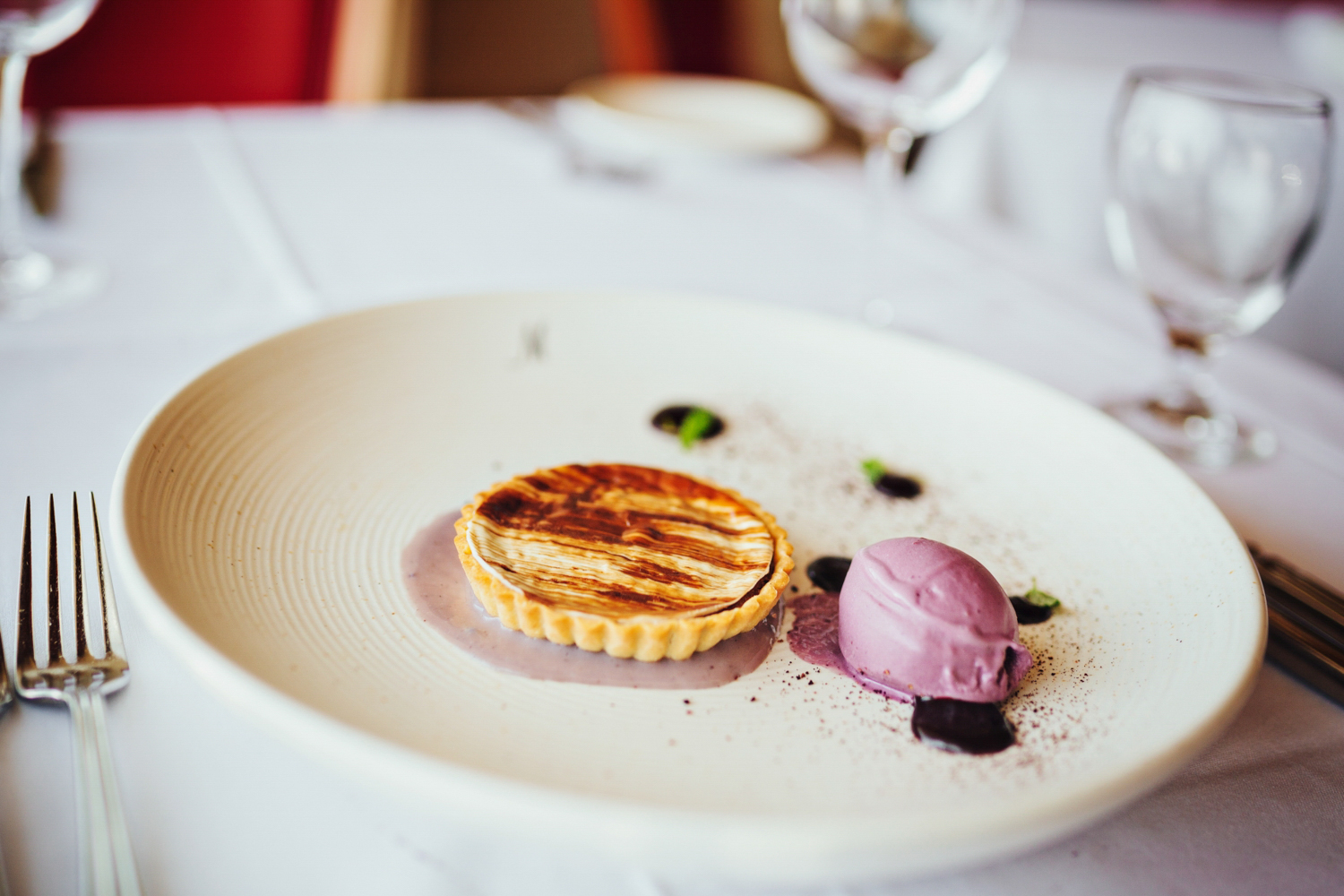 Beautiful image of delicious tart with berry ice cream quinelle in food photo shoot.