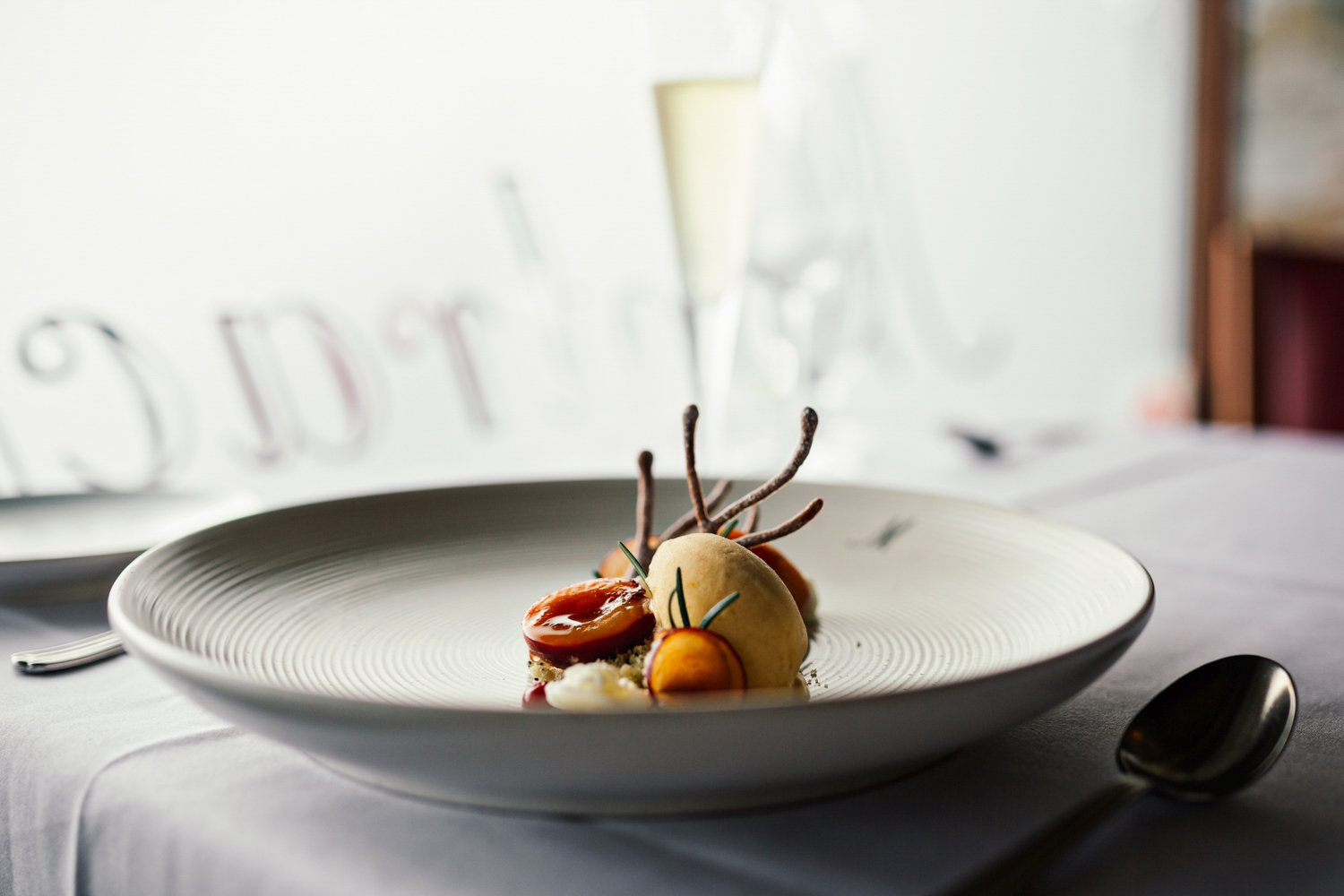 Professional photo of main meal served on white plate with white tablecloth in fine dining restaurant.
