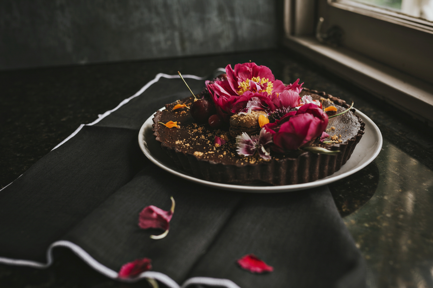 Chocolate tart with flowers and cherries sits on kitchen bench for food photography session.