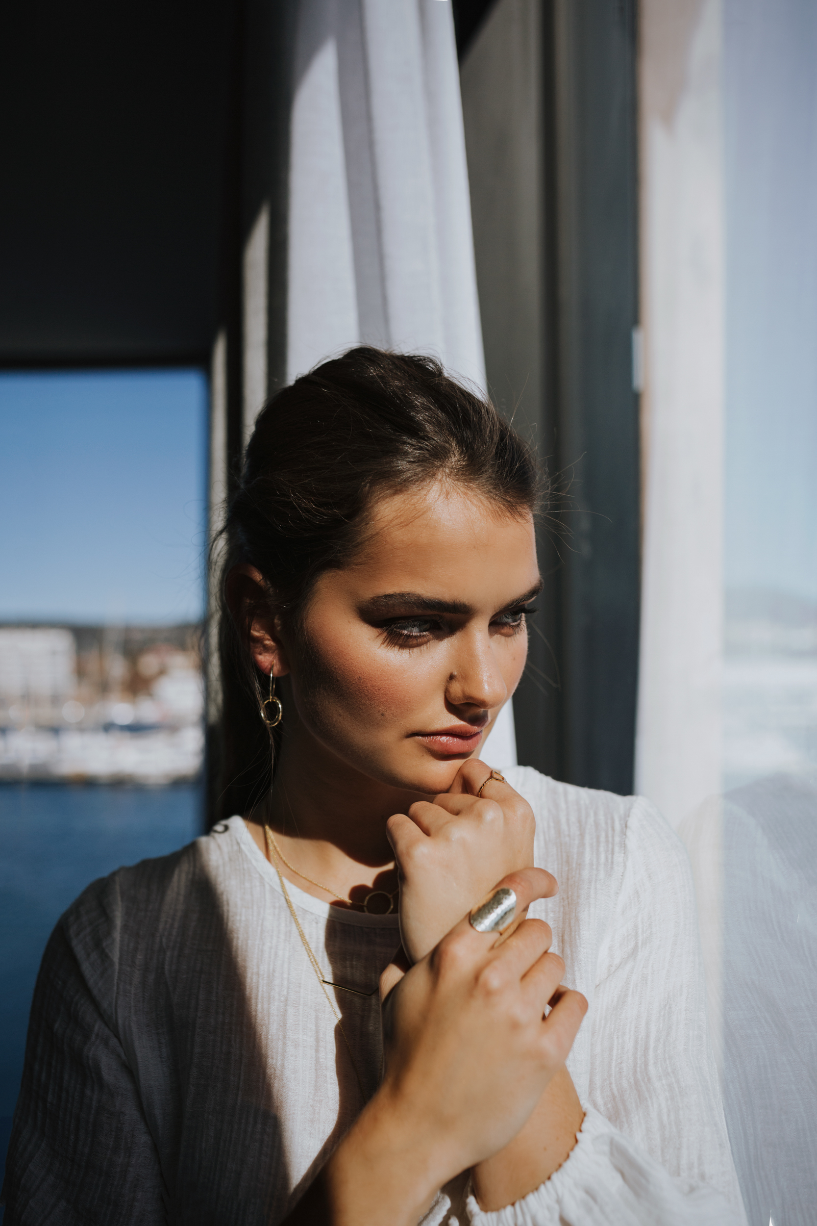 Model looks out of window on sunny day in Tasmania.
