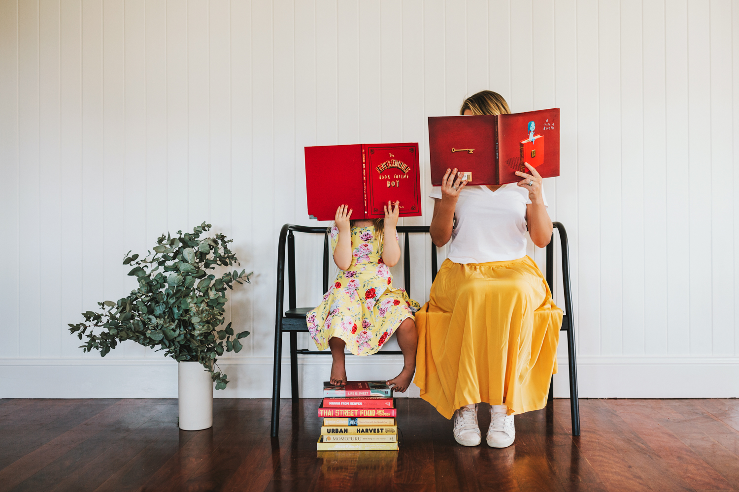 Woman and child sit and hide behind big red books.