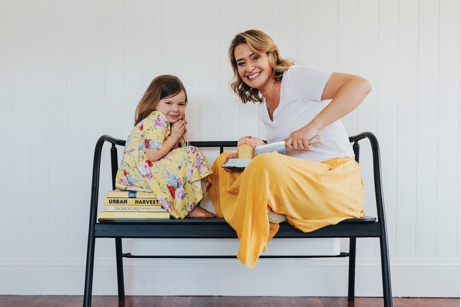 Woman and child sit on chair and share sponge cake and smile for