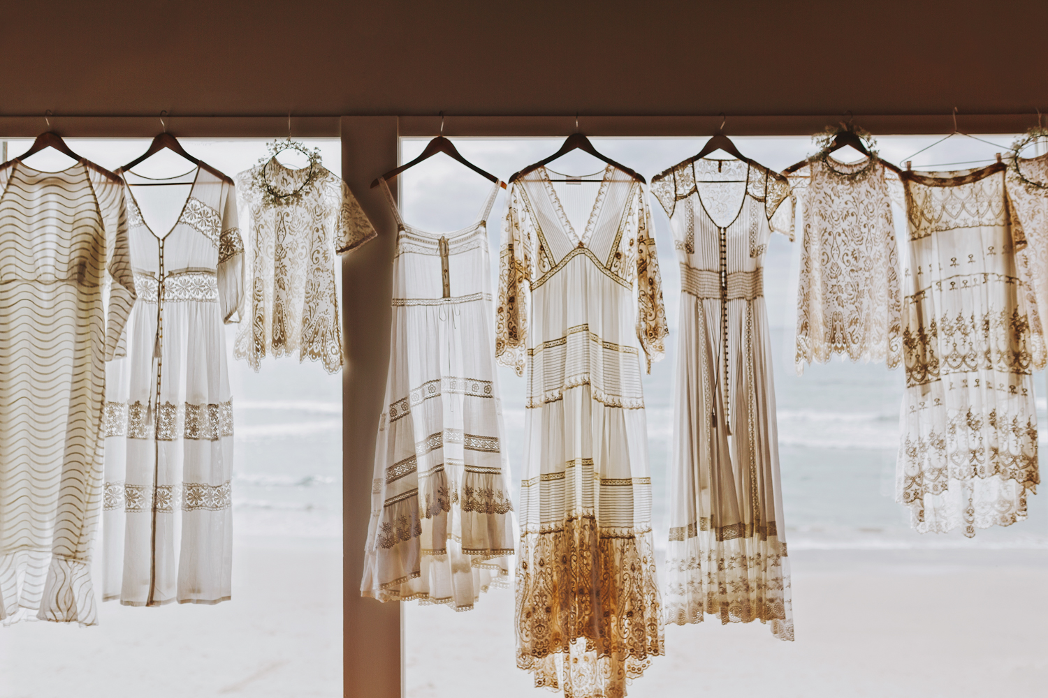 Beautiful Spell Designs wedding gowns hang at window.
