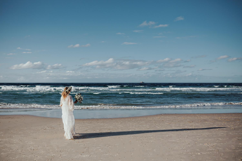 Bride walks toward ocean in Spell Designs gown in Byron Bay.