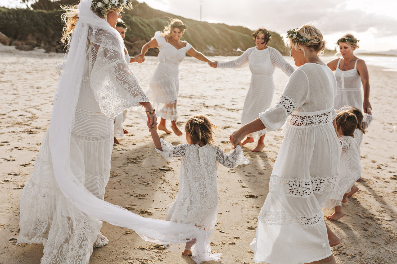 Bridesmaids and flowergirls dance on beach in relaxed wedding in