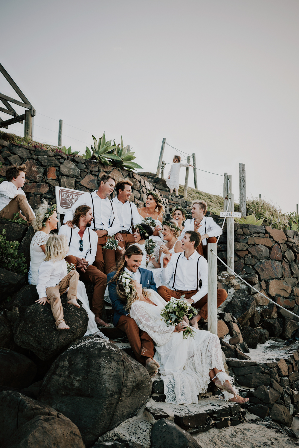 Bridal party laugh on steps of the beach.