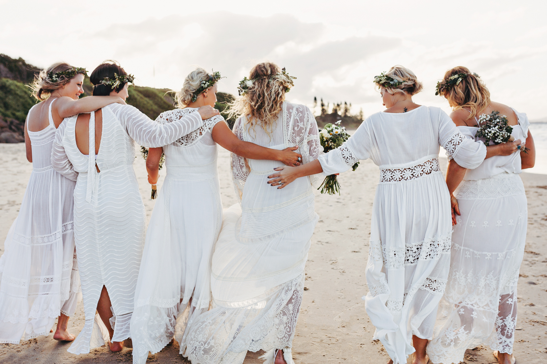 Bridesmaids walk arm in arm in Spell Designs wedding gowns.